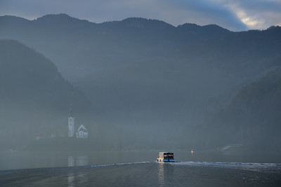 A ferry boad heads into the mist on Lake Bled