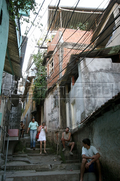 Tourists walk through a narrow alley of the Parque da Cidade slum during a tour in Rio de Janeiro, Brazil, August 23, 2005. Along with traditional tourist sites such as beaches, the Christ statue and Sugaloaf mountain, Rio's famous slums, which offer spectacular views of the city, are becoming a regular tourist stop.  (AustralFoto/Douglas Engle)