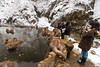 Tourists photograph snow monkeys as they sit in a hot spring (Japanese macaque, Macaca fuscata). Jigokudani Yaen-Koen near Shibu Onsen, Japan.