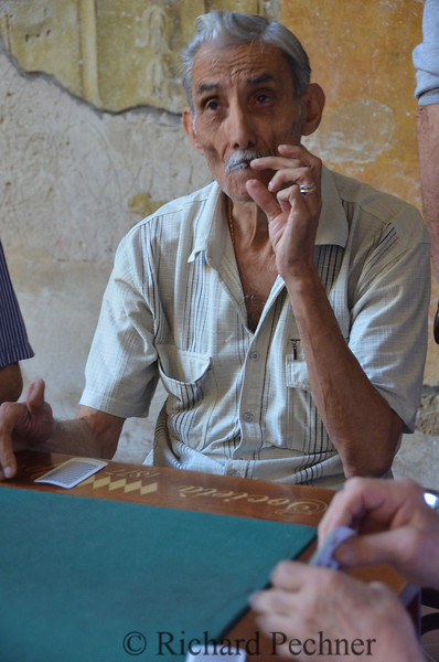dealer taking a drag as betting continues