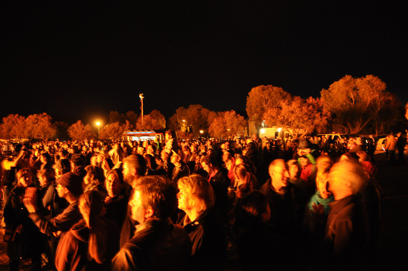 The fire lights-up the crowd and surrounding area.