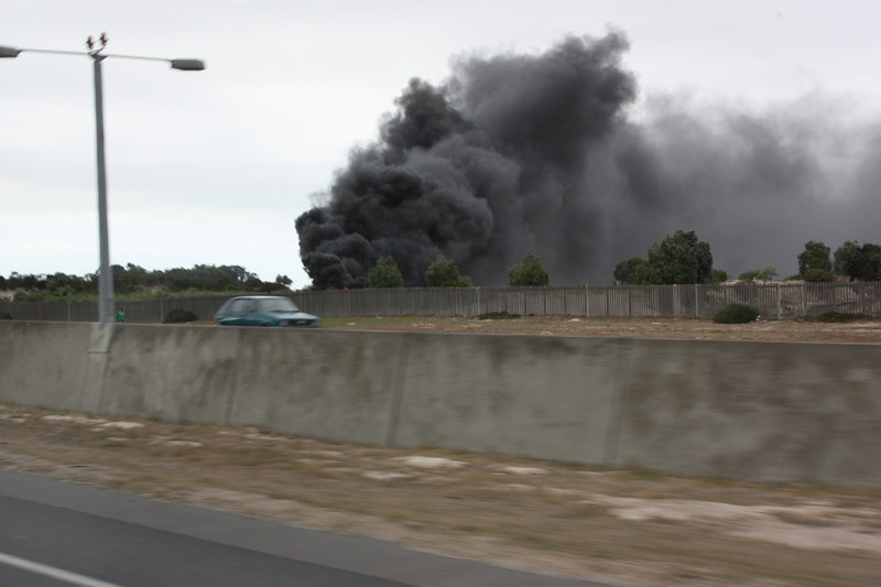 As we were heading to Stellenbosch, we passed by many shanties along the road.  In one instance they were burning tires.