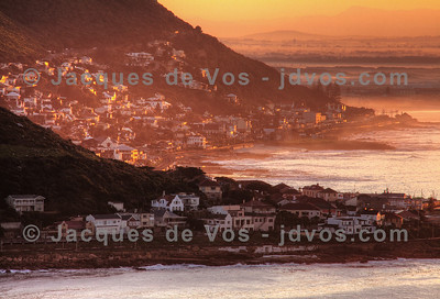 Sunrise - View from Fish Hoek towards Muizenberg.  Clovelly in front, Kalk Bay and St James in the middle with Muizenberg and the Cape Flats visible under mist in the back.