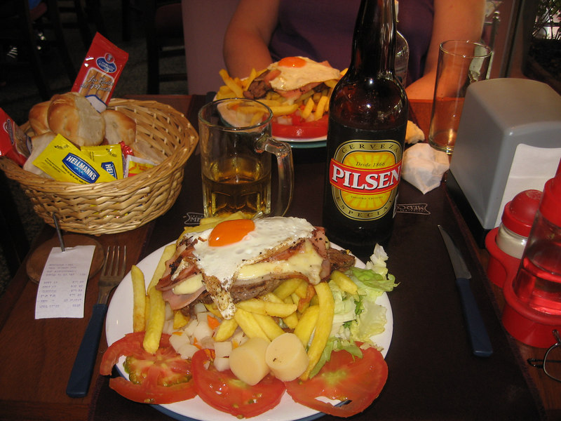 "The Uruguayan ""chivito"". Steak, tomato, lettuce, mayonnaise, cheese, ham, bacon, fried egg! This one is served atop a bed of french fries with potato salad on the side. Yummmm!"