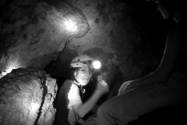 Celia climbing into cave