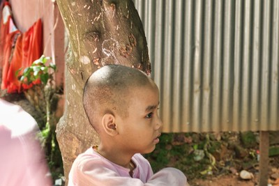 A young nun.  The young nuns wear pink robes.  They, like the monks, shave their heads.