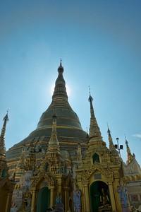 The noon sun behind a pagoda spire.