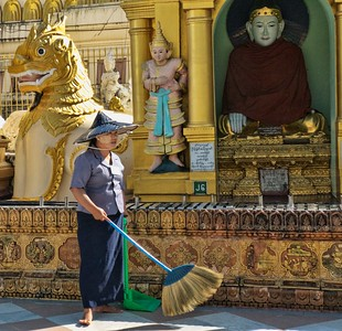 Many women with these large brooms keep the area clean.