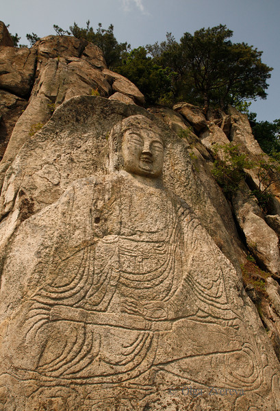 <p>Stone Seated Buddha, Mt.Namsan area, Gyengju, South Korea</p>  <p>This Buddha image is the biggest of the Buddha images in the Mt. Namsan and is located in Sangseonam Rock which is the highest spot on the mountain. This relief is 5.2m high, and the widht of its knee is 3.5m.</p>
