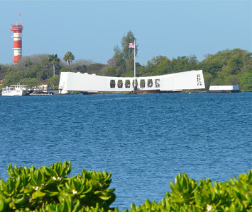 The low-slung white building of the Arizona Memorial floats in the water at Pearl Harbor on Oahu.