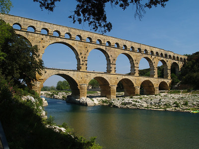 May 16, 2100.  The tri-leveled Pont du Gard stands proudly over the Gardon Valley as it did during the Roman era. The construction of the aqueduct took place in the first century AD. Designed to carry water across the valley, it was entirely constructed without the use of mortar over a period of three years, employing 1,000 workers. The Pont du Gard is now a UNESCO World Heritage site. Gardon Valley, Provence, France. You will see people walking across the bridge, on the lower level, if you enlarge this, to help put this impressive structure into perspective.