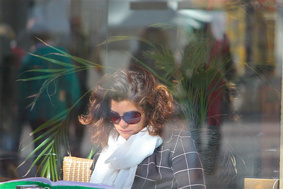 "April 25, 2012. I'm back from Provence. I took this photograph in Avignon one morning as I was crossing a square filled with cafes and restaurants. This young woman was sitting at a table and caught my eye. She looked so glamourous in the soft sunlight. I'm always very hesitant about taking strangers pictures and even though I really wanted to take the shot I continued to walk but something told me I'd always regret it so I got over my apprehension and quickly took one photograph of her. At this point I no longer had an unobstructed view of her. There were strong winds blowing gale force that day, the ""Mistral"" as the French call it and the woman was sitting behind a glass screen to protect her from the wind, the glass screen also reflected a couple strolling through the square. At first I was unhappy with the distraction of the reflection but the more I look at it the more I like it and think that the reflection adds to the interest of the composition."