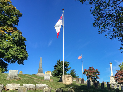 Confederate flag flies in the foreground over the Confederate soldiers' graves.  US flag flies im the background.