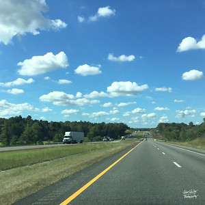 Beautiful October day on I-40.  Bright blue skills and summer-puffy white clouds.