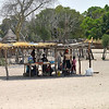 Women and children selling produce as a roadside stall.  Note the woman and child on the right balancing goods on their heads.<br /> This was a rather typical village and site in the Caprivi Strip of northeastern Namibia.