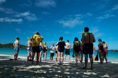 A group of snorkelers are given instruction before they dive in.