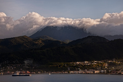Arriving at the beautiful island country of Dominica, the volcanic mountain peaks are surrounded by clouds.