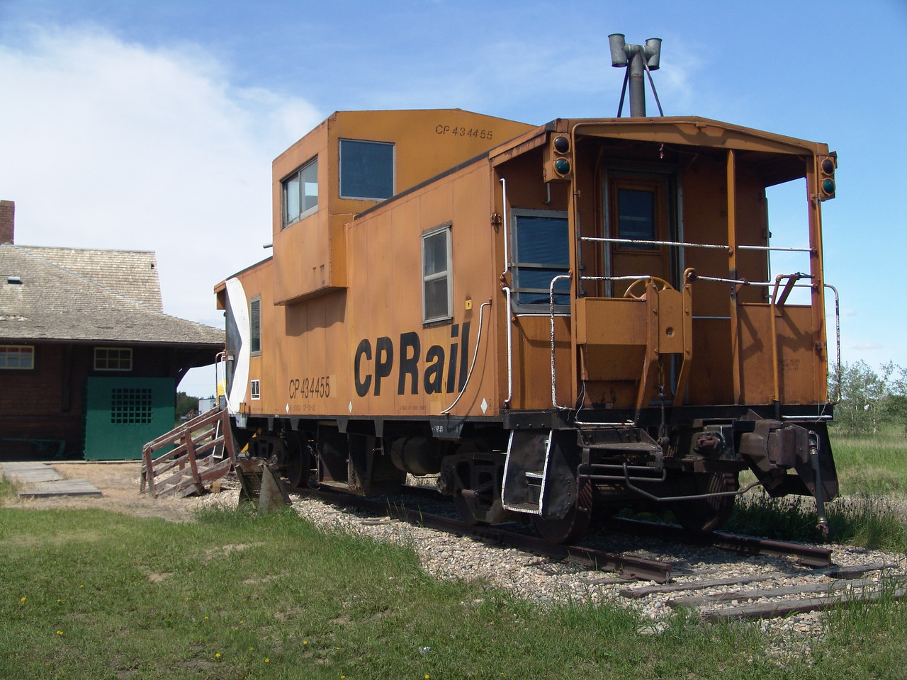 An old caboose on one length of railroad tracks.