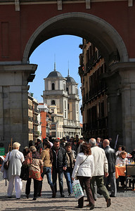 Madrid - View of Colegiata de San Isidro through one of the arched entrance ways to Plaza Mayor.