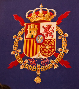 The castle is for Castile. The lion is for Leon. The stripes are for Aragon. The chains in the shield are for Navarre. The little pomegranate represents Granada. The fleurs-de-lit in the middle represent the House of Bourbon, the family of King Juan Carlos. The thing at the bottom represents the Order of the Golden Fleece, a chivalric order founded by one of the king's ancestors in the 1400s.