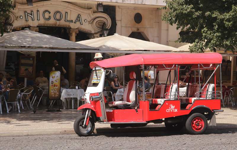 Tricycle taxi outside Cafe Nicola at Rossio Square Lisbon Portugal