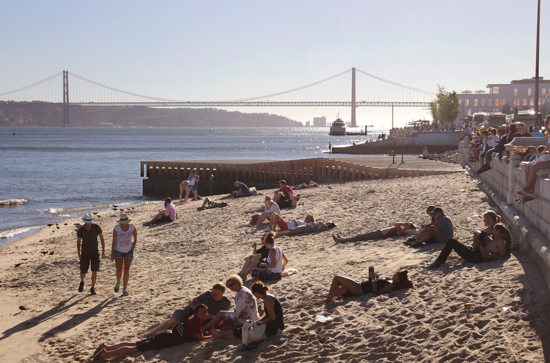 People relaxing near Praca do Comercio by River Tagus Lisbon Portugal