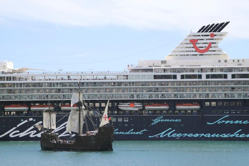 Santa Maria replica ship sailing past modern cruise liner at Funchal harbour Madeira