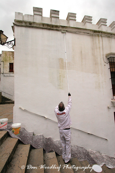 A painter touches up the paint on one of Arcos' white-washed structures. There is a reason these are called the pueblos blancos, or white towns.