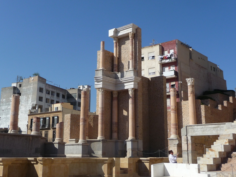 Parts of the Roman theater skene building in Cartagena, with neighboring apartment buildings.
