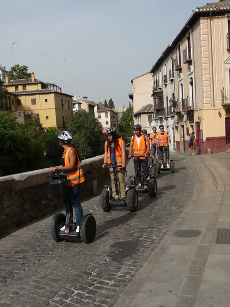 A group riding Segways up the steep hill of Douro Street in Granada. It looked fun to try and easier than walking!