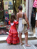 Cute girl in a flamenco dress looking at shawls in a shop window near the Cathedral