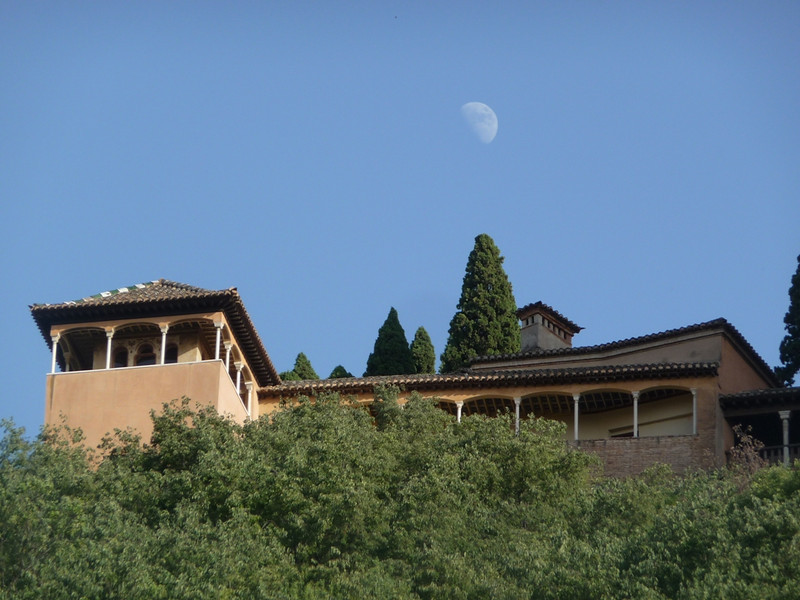 Alhambra buildings, with moon above, seen from across the way on another hill in the Albaicin in Granada.