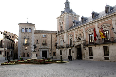 The largest building at the square is the Casa de la Villa or Town Hall (ayuntamiento). Construction started in 1644 by Juan Gómez de Mora, the architect of the Plaza Mayor. Over time a number of architects were in charge of the construction of the Town Hall until it was finished in 1696 by Teodoro Adremans. The building served both as town hall and prison, hence the two symmetrical doors. The left one gave entrance to the prison, the other one to the town hall.