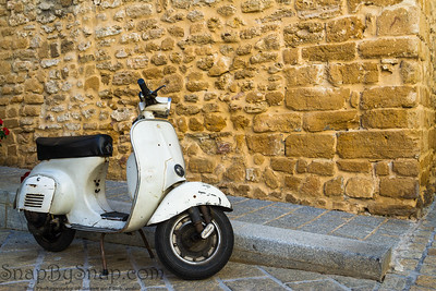 A vespa scooter parked in front of a aged wall.