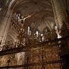 """La capilla mayor de la catedral de Toledo acumula una gran riqueza en obras de arte, empezando por la propia arquitectura del recinto. En su origen estaba separada en dos partes con dos bóvedas independientes. La bóveda poligonal pertenecía a la capilla de los Reyes Viejos que quedaba algo separada. Con esta división, el presbiterio resultaba algo estrecho y no muy propio de semejante catedral. El cardenal Cisneros tuvo muy claro reconstruir esta parte de la catedral y tras algunas situaciones de enfrentamiento con el Cabildo, consiguió el consentimiento para demoler la dicha capilla de los Reyes Viejos, hacer el presbiterio más amplio y dar espacio suficiente para el gran retablo gótico que él mismo había encargado.<br /> <br /> También en su origen, la capilla estaba cerrada lateralmente por dos magníficas """"rejas"""" de piedra, que eran como enormes cancelas. La parte correspondiente al Evangelio fue destruida al hacer el mausoleo del cardenal Mendoza. Queda la parte correspondiente a la Epístola y por ella puede deducirse que se trataba de un gran trabajo. Está copiosamente decorada de estatuaria y rematada por un coro de ángeles que parecen ir volando. En armonía con esta obra de piedra calada se construyeron los dos pilares que dan paso al interior de la capilla. En el pilar de la izquierda hay una figura con barba y cayado de pastor, el famoso pastor llamado Martin Alhaja que (según la leyenda) dio información en la Batalla de Las Navas de Tolosa; el pilar contrario se llama del Alfaquí por la estatua de este personaje Abu Walid quien llevó al rey Alfonso VI un mensaje de tolerancia (véase la sección La catedral de Alfonso VI)."""