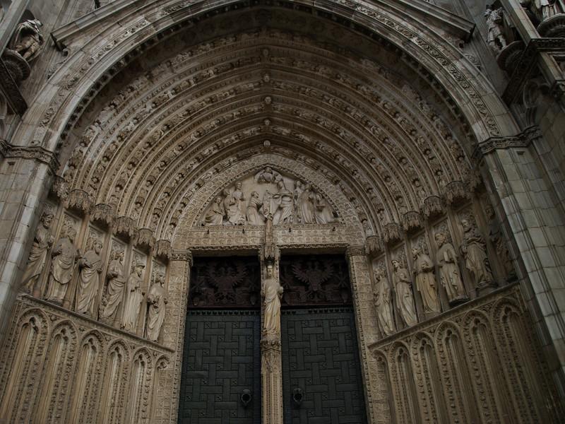Catedral de Toledo (Puerta de los Leones). Del siglo XV y XVI. Es la más moderna de las grandes puertas. Se llama así por los leones que coronan las columnas de la reja que cierra el pequeño compás. Tiene además otros dos nombres:<br /> Puerta Nueva, al ser la última que se construyó. <br /> Puerta de la Alegría, en alusión a la celebración de la Asunción de la Virgen que está representada en el testero del fondo, tras las arquivoltas. <br /> <br /> Se construyó entre los años 1460-1466, bajo el mandato del arzobispo Alonso Carrillo de Acuña; con trazas de Hannequin de Bruselas y Egas Cueman en colaboración con los escultores flamencos Pedro y Juan Guas y Juan Alemán, autor del Apostolado. Estos artistas estaban al frente de un gran taller que contaba con prestigiosos canteros y entalladores.<br /> <br /> La estatuaria de la puerta es uno de los mejores conjuntos hispano-flamencos del siglo XV, sobre todo la Virgen del parteluz y las estatuas de las jambas. Los querubines y ángeles músicos que acompañan la subida de María a los cielos son obras de arte ejecutadas con gran delicadeza. La fachada fue alterada por Durango y Salvatierra en el siglo XVIII, igual que en las otras puertas, para consolidar el edificio. Los once medallones situados por encima de la última arquivolta representan a profetas y patriarcas; el del centro representa a la Virgen María. Remata la puerta una gran estatua de San Agustín orante.<br /> <br /> Los batientes de bronce de las puertas son una obra maestra de Francisco de Villalpando, que hizo una gran labor en los 35 tableros o planchas. Están ocultas a la vista, protegidas con paneles de madera. Por encima puede verse el gran rosetón de vidrieras policromadas.<br /> <br /> En la parte baja del gran frontis está la puerta dividida por parteluz. Sobre la puerta se ve el tímpano esculpido con temas de la genealogía de la Virgen (árbol de Jesé), cuyos autores fueron los mismos que trabajaron en el exterior de esta puerta. Por encima del tímpan