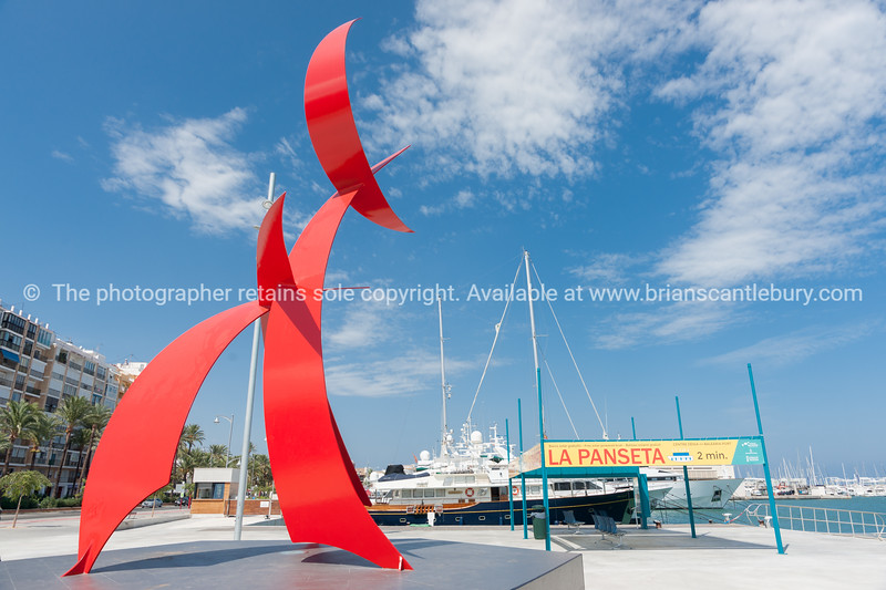 Portal Del Vent, large red sculpture on Denia waterfront, Spain.