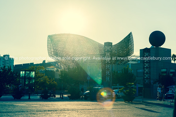 Stunning Frank Gehry fish sculpture shot into sun with lens flare and split tone filter effect on Barcelona waterfront Olympic Village