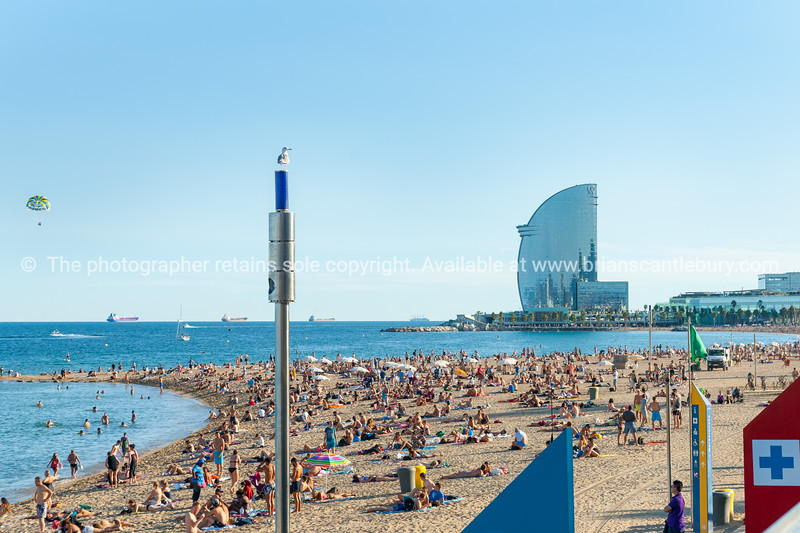 Barcelonetta Beach with architecturally modern W Hotel in distance, paraglider above and cargo ships on horizon sunbathers along sandy beach Barcelona Spain
