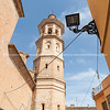 Alcalali church spire rising through narrow typically historic Mediterranean village street, Spain.