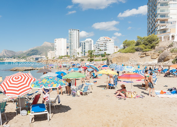 People sunbathing, sheltering under umbrellas on beach Calpe, Alicante Spain.