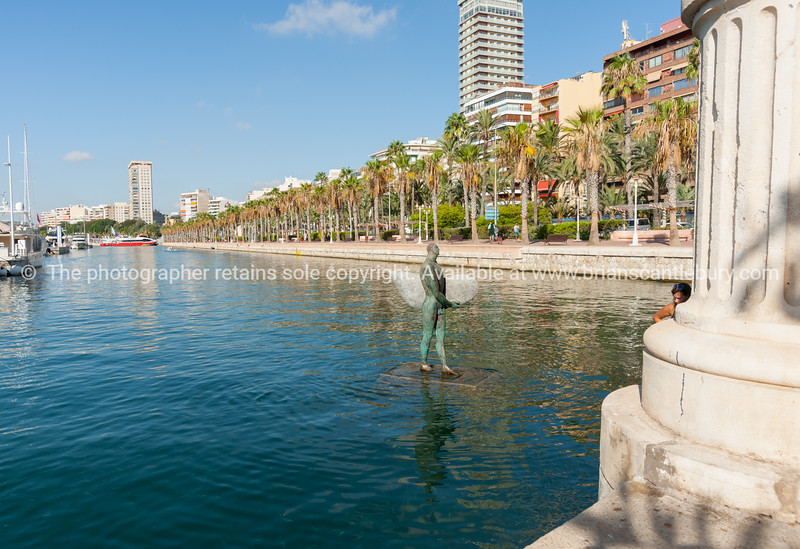 Icarus with broad shoulders with little head carrying a surf board in marina harbor. Alicante, Spain