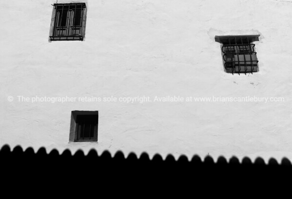 Three windows in white wall and roof shadow along base.