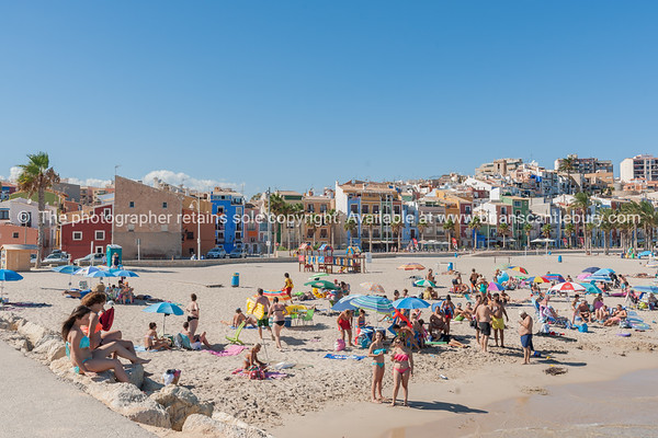 Colorful homes and buildings form backdrop to busy summer Mediterranean beach crowded with people and sun umbrellas, La Vila Joisa, Alicante Spain