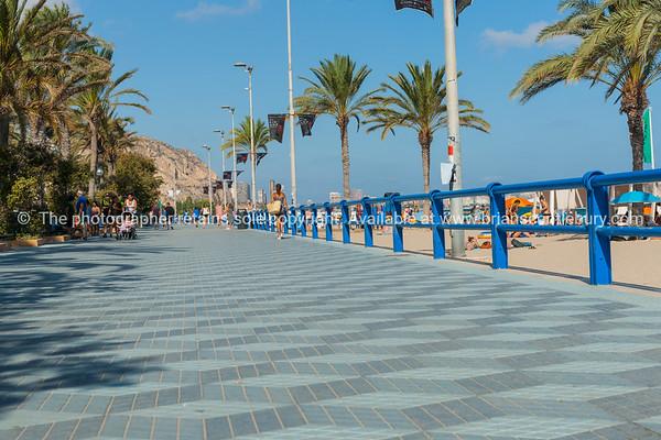 Promenade along  Postiguet Beach people walking in distance  Alicante Spain street and building scene