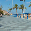 Promenade along  Postiguet Beach people walking in distance  Alicante Spain street and building scene