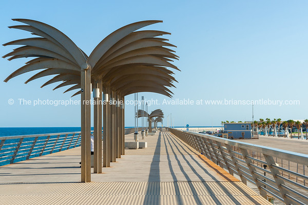 Sculptural palm trees on on the seaside esplanade at Muelle de Levante in the tourist resort elevated pedestrian walkway above breakwater, Alicante Spain