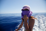 Crew member Shiho protects her face from the sun.