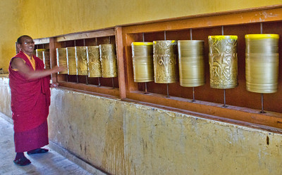 A lama turns the Tibetan prayer wheels clock-wise, as is their custom.