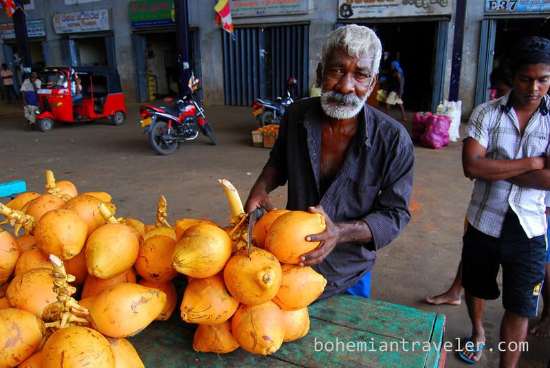 Cutting a King Coconut at Dambulla wholesale market in Sri Lanka.